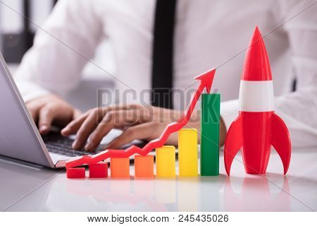 Rocket And Multi Colored Graph With Arrow In Front Of Businessperson Working On Laptop