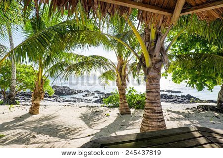 View From A Tropical Bar Onto Sandy And Rocky Beach With Palm Trees At Lefaga, Upolu Island, Western