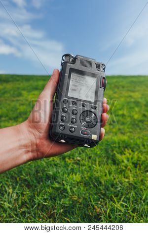 portable audio recorder in hand field recording ambient sounds of nature poster
