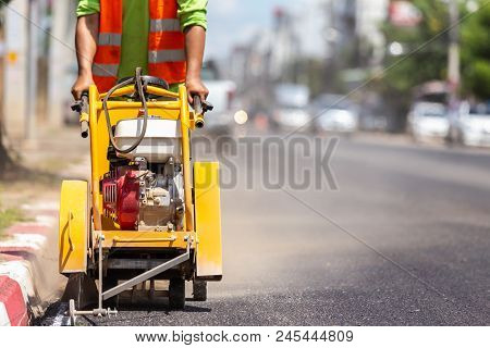 Worker Using Machine To Cut The Asphalt Road. Process Of Building New Road