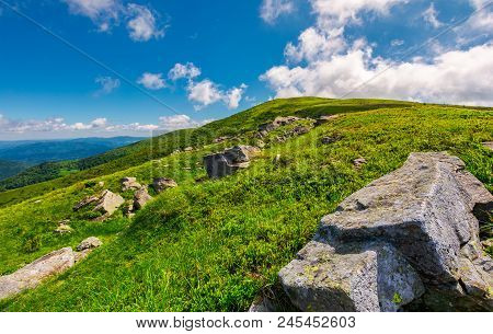 Lovely Summer Landscape. Grassy Hillside With Rocky Formations. Cloud Behind The Mountain Top. Brigh