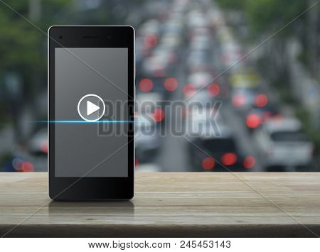 Play Button On Modern Smart Phone Screen On Wooden Table Over Blur Of Rush Hour With Cars And Road,