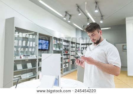 Handsome Bearded Man Is In The Electronics Store In The Phone Department And Chooses A Smartphone. B