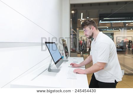 Man Uses A Computer In A Modern Electronics Store. Buyer Selects A Monoblock In A Light Technology S