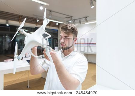 Handsome Man In A Modern Light Dron Store. Choosing And Buying A Quadcopter In The Electronics Store