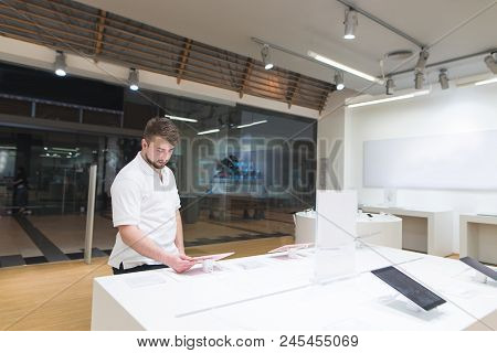 Man's Portrait Who Stands At The Shop Window And Selects Gadgets. The Buyer Looks At Gadgets In The