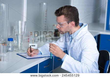 Researching Results. Adult Clever Handsome Discoverer Sitting On The Chair In The Laboratory Keeping