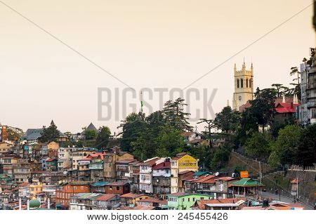 Shimla, India - 27th Apr 2018: Church On The Horizon Behind Some Trees And Lots Of Buildings In The