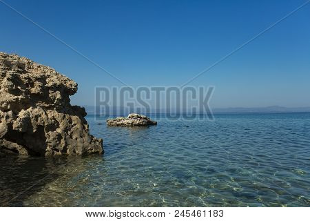 Stony Shore On Idyllic Seascape. Rock In Sea Water On Sunny Blue Sky. Wild Nature, Environment And E