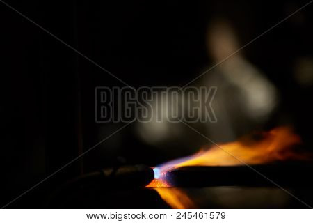 Treatment Of Molten Metal In The Blacksmith Workshop On Blurred Background, Close-up. Old-fashioned