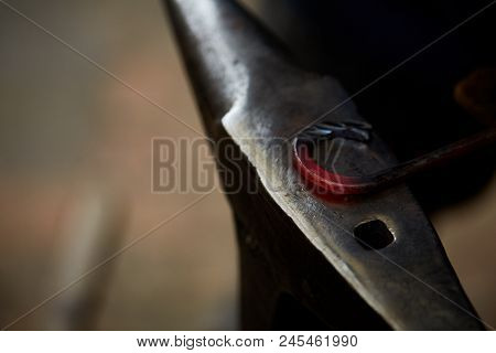 Hot Shaped Metal Laying On Anvil In The Blacksmith Workshop, Blurred Background. Metalsmithing Indus
