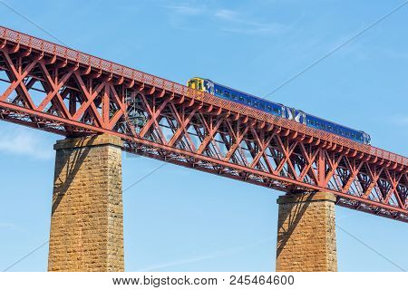 Forth Bridge, Railway Bridge Over Firth Of Forth Near Queensferry In Scotland With Train Passing The