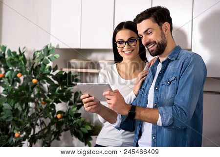 Nice News. Cheerful Yougn Lovng Couple Using Tablet While Resting At Home