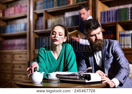 Student Life In University. Couple In Library With Typewriter And Teapot Drinking Coffee From Cup. L