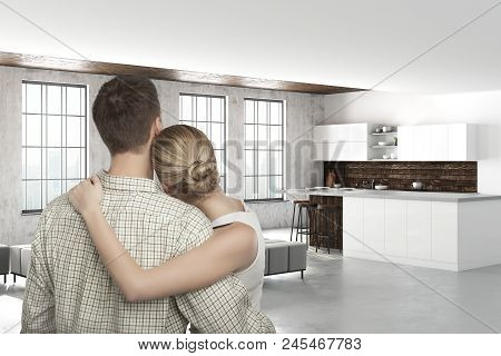Back View Of Young Caucasian Couple In Modern Kitchen Interior. Real Estate, Mortgage And Dream Conc