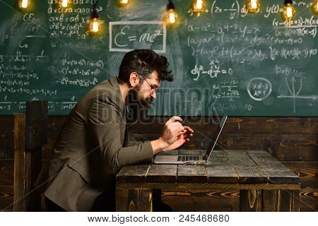 Bearded Man Work On Laptop In Classroom. Man With Long Beard With Computer On Chalkboard. Businessma