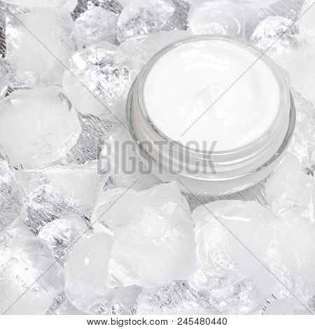 Close-up Of Open Glass Jar With Cream Surrounded By Ice Cubes. Cooling Effect Skin Care Product