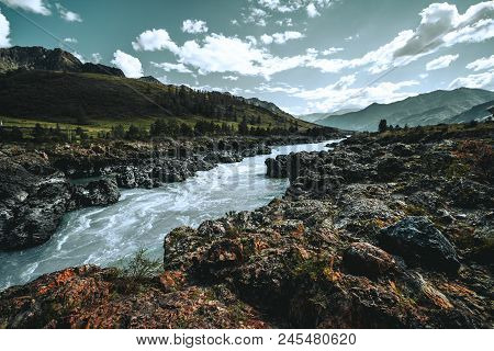 Wide-angle Shot Of A Cliffy Contrast Mountain Riverside Overgrown With Moss And Native Grasses, With
