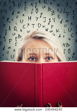 Close Up Portrait Of Pretty Student Girl Hiding Behind A Red Opened Book With Lating Alphabet Letter
