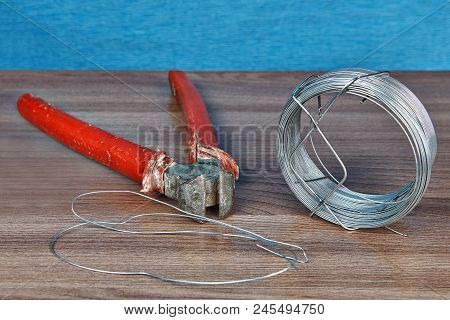 End cutting nipper with red handles and one roll of steel wire. poster