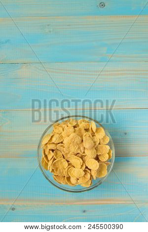 Tasty Cornflakes In Glass Bowl On Blue Background. Top View
