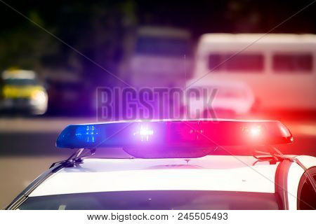The Blinkers Of A Police Car On A Blurred Background. Blue And Red Flashing Light. Danger. Crimes. T