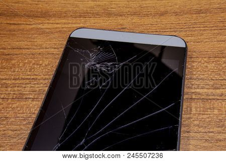 Black Mobile Phone On The Wooden Table With Crashed Lcd Display. Mobile Technology Concept. Crashed