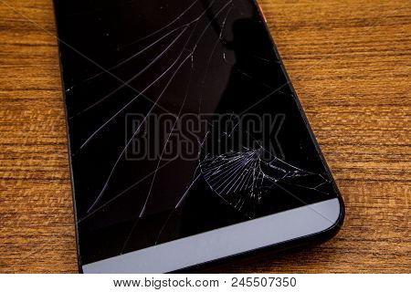 Crashed Mobile Phone On The Table. Black Mobile Phone On The Wooden Table With Crashed Lcd Display.