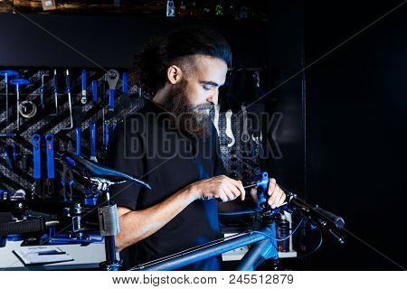 Theme Sale And Repair Of Bicycles. Young And Stylish With A Beard And Long Hair, A Caucasian Man Use