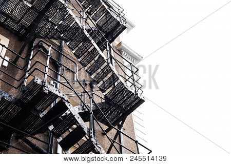 Metal Construction On The Building. Fire Stairs On The Old Building. Building Made Of Bricks. Frog P