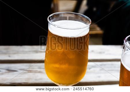 Glass Of Beer On The Wooden Table. Draft Beer Served At The Bar. Glass Of Light Beer On The Wooden B