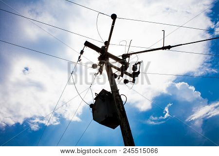 High Voltage Post With Sunny Blue Sky. High Voltage Tower With Sky In The Background. Silhouette Of