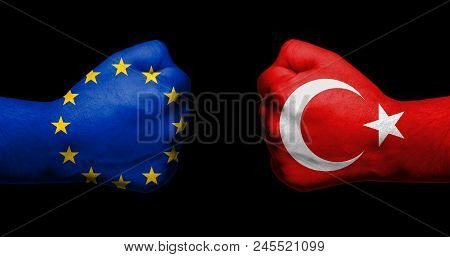 Flag Of European Union And Turkey Painted On Two Clenched Fists Facing Each Other On Black Backgroun