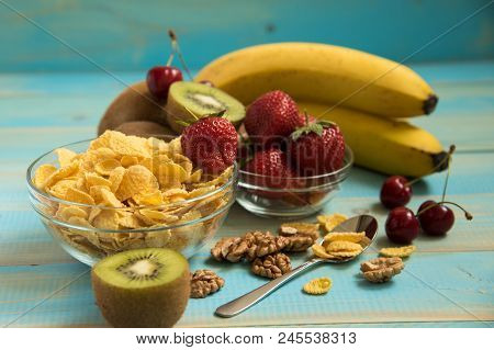 Tasty Cornflakes In Glass Bow With Walnut And Strawberries, Bananas, Kiwi On Blue Background. Corn F