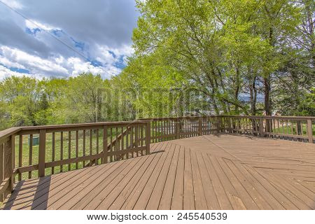 Wooden Deck With Cloudy Skies And Green Trees. Wide Angle.