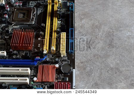 Black Motherboard Of Computer On Grey Grunge Table Background With Copy Space For Text. Electronic C