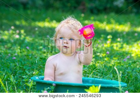 Toddler Baby Girl With Blue Eyes  Having Fun With Water