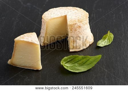 Crottin Cheese With Basil Leaves On Black Stone Background