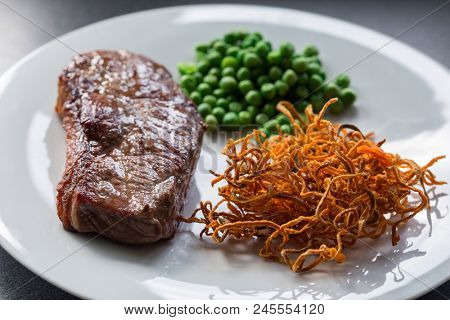 Close up image of a piece of medium rare chargrilled steak with green peas and crispy sweet potatoes