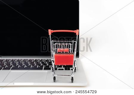 Shopping Cart On A Laptop Keyboard Isolated On White Background, E-commerce, Shopping Cart On Laptop