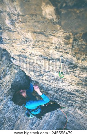 The Girl Climbs The Rock. A Woman Overcomes A Difficult Climbing Route. A Rock Climber On A Rock. Do