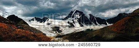 Beautiful Dramatic Mountain Landscape. Dark Mountains And Glacier On The Background Of Dark Snow Clo