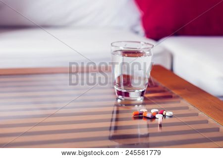 Pills Capsules Medicine And Glass Of Water On The Table. Medicine, Heathcare Concept