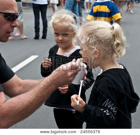 Twins enjoy ice cream from father.