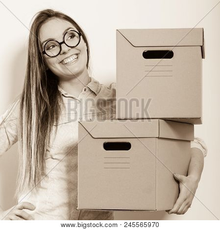 Happy Woman Moving In Carrying Cartons Boxes. Young Girl Arranging Interior And Unpacking At New Apa