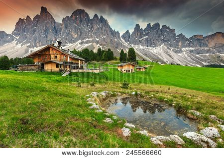 Amazing Alpine Landscape With High Peaks, Wooden Chalets And Mountain Lake. Famous Geisler - Odle Pe