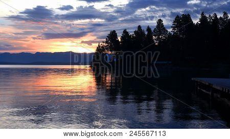 Sun rising above the Swan Mountain Range and Flathead Lake in Montana
