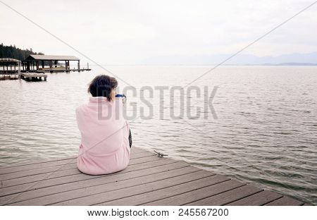 Middle aged caucasian woman sitting on lakeside dock drinking cup of coffee on a stormy mountain morning