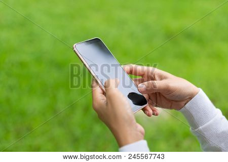 Close-up Image Of Woman Hands Using Smartphone, Hand Of Woman Using Smartphone On Green Background,