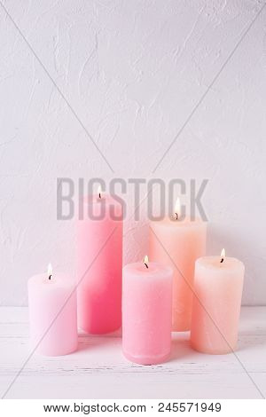 Diffenent  Pink  Burning Candles On White Textured Background. Vertical Image. Selective Focus.